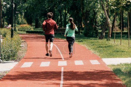 Back view of young couple jogging together on running track in park