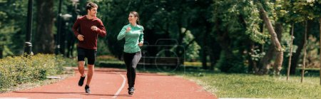 Panoramic crop of couple smiling at each other while jogging in park