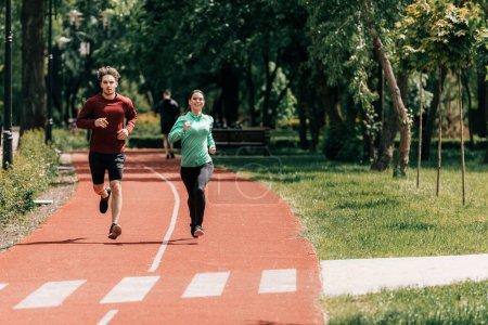 Photo pour Femme souriante courant près beau petit ami sur la piste de course dans le parc - image libre de droit