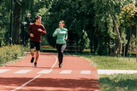 Photo pour Couple souriant tout en faisant du jogging sur la piste de course dans le parc - image libre de droit