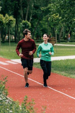 Photo pour Concentration sélective de la sportive souriant au petit ami tout en faisant du jogging dans le parc - image libre de droit