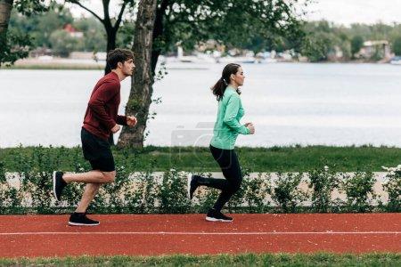 Photo pour Vue latérale du couple courant sur la piste de course dans le parc - image libre de droit