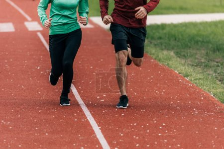 Photo for Cropped view of couple jogging together on running track in park - Royalty Free Image