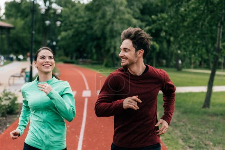 Photo for Smiling man looking at positive girlfriend while jogging in park - Royalty Free Image