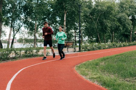 Photo for Smiling young couple running together on running path in park - Royalty Free Image