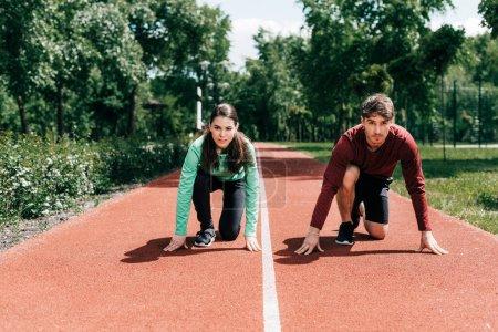 Photo pour Couple debout en position de départ sur la piste de course dans le parc - image libre de droit