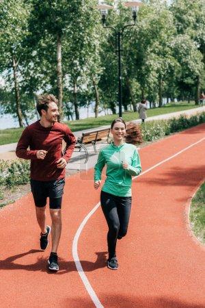 Photo pour Beau homme souriant près de petite amie pendant le jogging dans le parc - image libre de droit