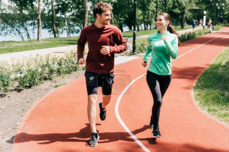 Photo for Sportswoman smiling at boyfriend while running on track in park - Royalty Free Image