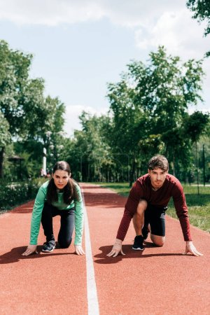 Photo pour Jeune couple en position de départ sur piste de course dans le parc - image libre de droit