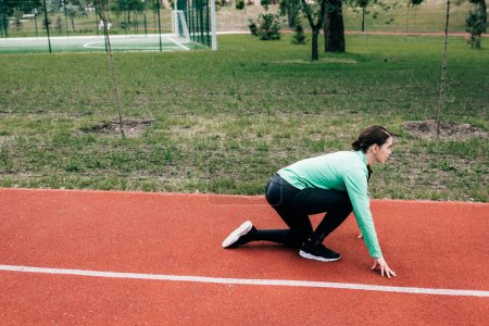 Photo for Side view of sportswoman in starting position on running path in park - Royalty Free Image
