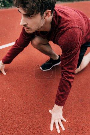Photo pour Beau sportif en position de départ avant de courir sur la piste dans le parc - image libre de droit