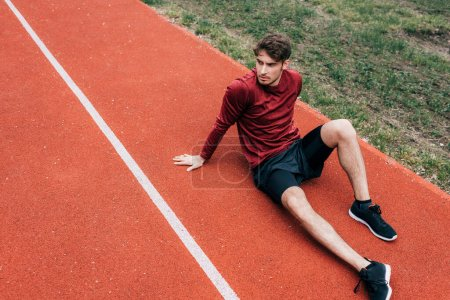 Photo for Handsome sportsman sitting on running track in park - Royalty Free Image