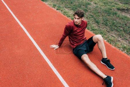 Photo pour Beau sportif assis sur la piste de course dans le parc - image libre de droit