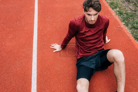 High angle view of handsome sportsman sitting on running track in park