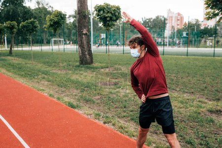 Photo for Sportsman in medical mask exercising on track in park - Royalty Free Image