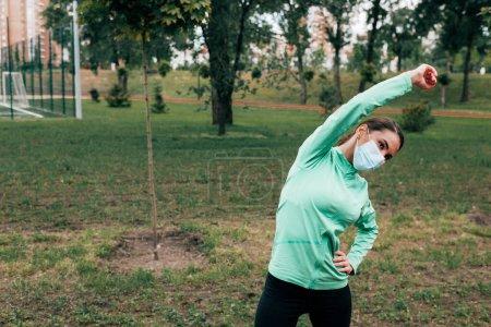 Photo pour Femme sportive en masque médical faisant de l'exercice dans le parc - image libre de droit