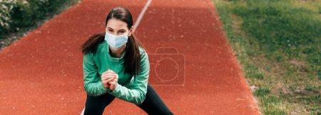 Photo pour Prise de vue panoramique de sportive en masque médical faisant squat sur piste de course dans le parc - image libre de droit