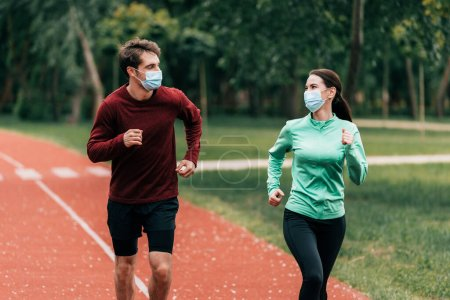 Photo for Young couple in medical masks jogging on running track in park - Royalty Free Image