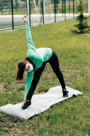 Photo for Sportswoman in medical mask training on fitness mat in park - Royalty Free Image
