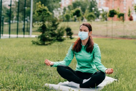 Photo for Young woman in medical mask meditating on fitness mat in park - Royalty Free Image