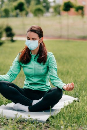 Photo for Selective focus of young woman in medical mask meditating on fitness mat in park - Royalty Free Image