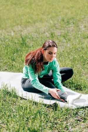 Selective focus of attractive sportswoman stretching on fitness mat on grass in park