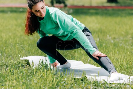 Selective focus of sportswoman warming up on fitness mat in park