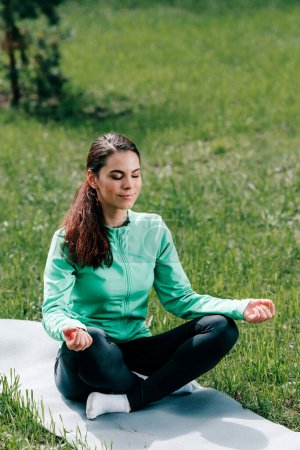 Photo for Attractive woman meditating on fitness mat on grass in park - Royalty Free Image