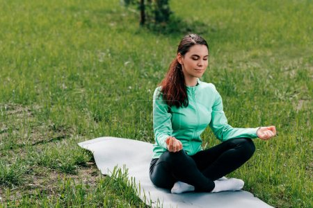 Beautiful woman with crossed legs meditating on fitness mat on grass in park