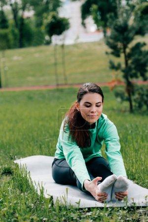 Selektiver Fokus der schönen Sportlerin beim Dehnen auf der Fitnessmatte im Park