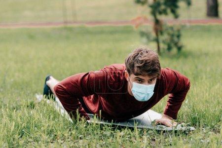 Enfoque selectivo del deportista en máscara médica haciendo flexiones en la estera de fitness en el parque