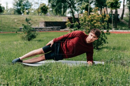 Photo for Selective focus of handsome sportsman doing side plank while training on fitness mat in park - Royalty Free Image