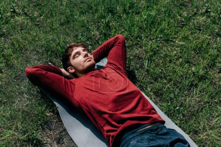 High angle view of handsome sportsman lying on fitness mat in park