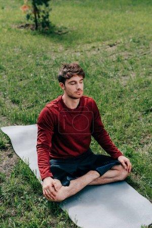 Photo pour Bel homme avec les yeux fermés assis dans la pose de yoga sur tapis de fitness dans le parc - image libre de droit