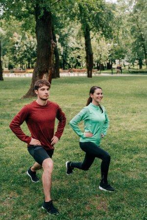 Photo pour Sportive souriante faisant des fentes près de petit ami dans le parc - image libre de droit