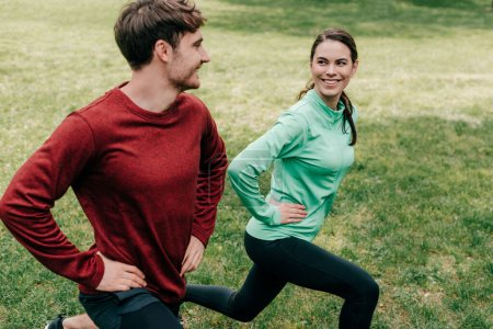 Selective focus of sportswoman smiling at boyfriend while training on grass in park