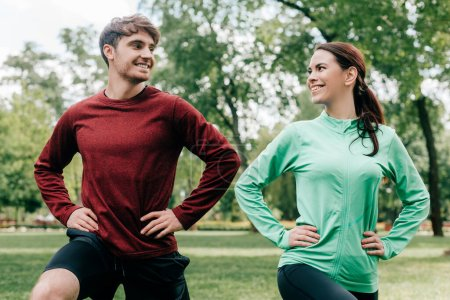 Young couple smiling at each other while training together in park