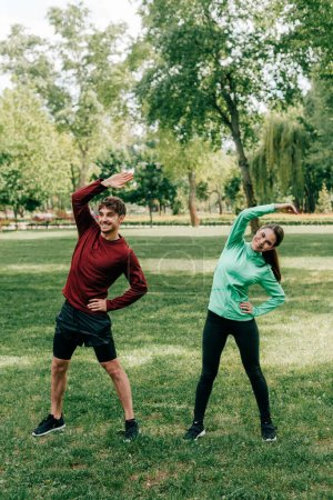 Young smiling couple working out on grassy lawn in park