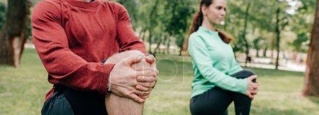 Concentration sélective des jeunes couples s'étirant dans le parc, culture panoramique