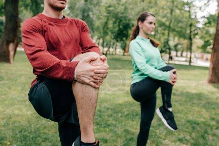 Photo pour Foyer sélectif de couple étirant les jambes tout en travaillant dans le parc - image libre de droit