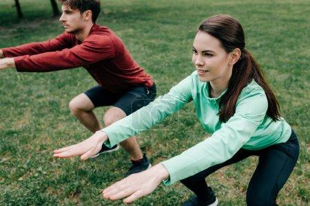Photo pour Concentration sélective de la sportive souriante faisant squat tout en travaillant près de petit ami dans le parc - image libre de droit