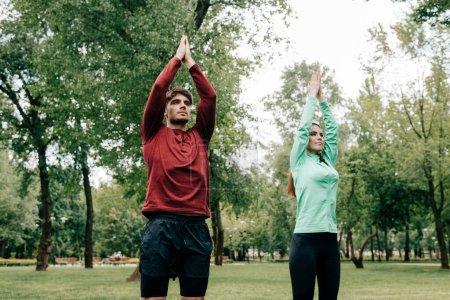 Pareja joven haciendo ejercicio juntos en el césped en el parque