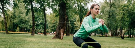 Panoramic crop of sportswoman doing squat with resistance band in park