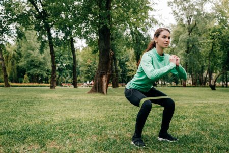 Photo for Attractive sportswoman doing squat with resistance band in park - Royalty Free Image
