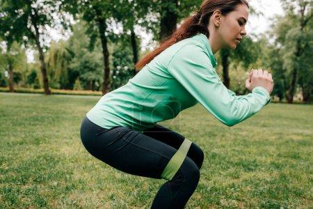 Photo pour Vue latérale de la sportive faisant squat avec bande de résistance sur l'herbe dans le parc - image libre de droit