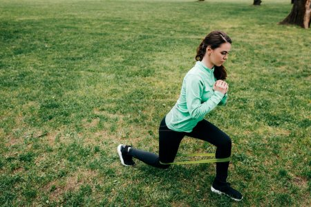 Photo for Side view of attractive sportswoman doing lunges with resistance band in park - Royalty Free Image