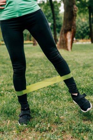 Photo pour Vue recadrée d'une sportive utilisant une bande de résistance pendant son entraînement dans un parc - image libre de droit