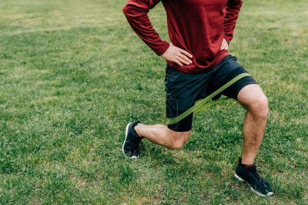 Photo for Cropped view of sportsman doing lunges with elastics band in park - Royalty Free Image