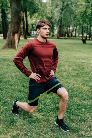Handsome sportsman doing lunges while training with resistance band in park
