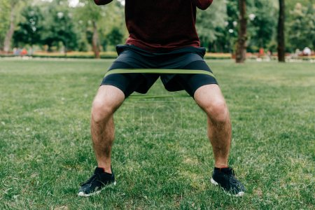 Photo for Cropped view of young sportsman using resistance band while working out in park - Royalty Free Image